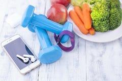 Sportuitrusting, blauwe domoren en vruchten, groenten en telefoon Geschiktheidsarmband en hoofdtelefoons voor muziek Vrije ruimte stock fotografie