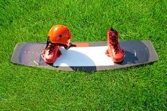 Sportuitrusting voor wakesurf - een kielzograad, laarzen, een helm en een wakesurfing vest die op het groene gras liggen stock afbeelding