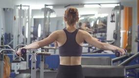 Sportunga flickan som gör sidohanteln, lyfter, medan sitta på sportbänk i en idrottshall Fps för sikt för tillbaka sida 60 stänge arkivfilmer