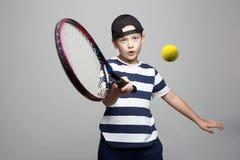 Sportunge Barn med den tennisracket och bollen royaltyfria foton