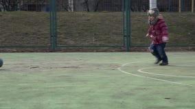 Sportunge Leka fotboll för flicka Behandla som ett barn med bollen på sportfält lager videofilmer