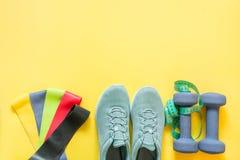 Sportutrustning, gummiband, hantlar, konditionskor som mäter bandet på guling royaltyfri fotografi
