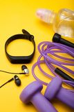 Sportutrustning Hantlar, överhopprep, konditionarmband, vatten och hörlurar på en gul bakgrund arkivfoto