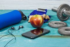 Sportutrustning Hantlar fria vikter, sporthandskar, telefon med hörlurar Arkivbilder