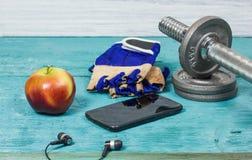 Sportutrustning Hantlar fria vikter, sporthandskar, telefon med hörlurar Royaltyfria Bilder
