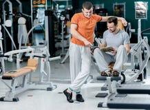 Sportvriendschap Zit jonge glimlachende atleet twee onder trainers i stock foto