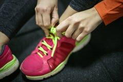 Sportvrouw Bindend Kant op Tennisschoenen Stock Afbeelding
