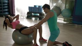 Sportvrouw die apdominalkraken op de pilatesbal doen stock footage