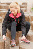 Sportvrouw die bij de schoenen van de onderbrekingsoefening wordt gebonden royalty-vrije stock afbeelding