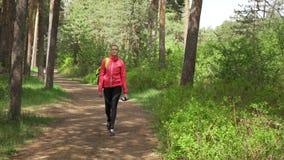 Sportvrouw die de bos achter het parkfitness van de meningsherfst vrouwelijke openluchtzon van de meisjesochtend lopen stock videobeelden