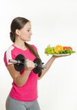Sportvrouw die een plaat van fruit bekijken terwijl het houden van een domoor in de andere hand Stock Fotografie
