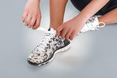 Sportvrouw die haar schoenveters binden vóór de opleiding Sluit omhoog Royalty-vrije Stock Foto
