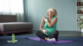 Sportvrouw die op middelbare leeftijd schouderpijn na training, gezamenlijke ontsteking voelen stock fotografie