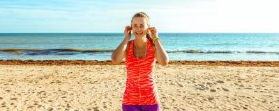 Sportvrouw die op zeekust met hoofdtelefoons aan muziek luisteren royalty-vrije stock foto
