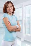 Sportvrouw die sportenkleren met gekruiste wapens dragen die bekijken Stock Foto
