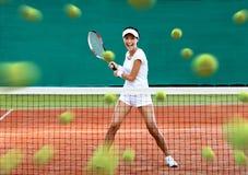 Sportvrouw die veel tennisballen terugkeren Stock Afbeelding