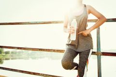 sportvrouw die zich na het lopen met het water van de handholding bottl bevinden stock fotografie