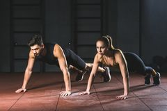 Sportvrouw en sportman die duw UPS in gymnastiek doen royalty-vrije stock fotografie