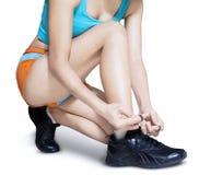 Sportvrouw het binden rijgt haar schoen stock afbeelding