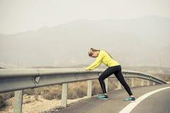 Sportvrouw het uitrekken zich beenspier na het runnen van training op asfaltweg met droog woestijnlandschap in harde fitness ople Stock Foto's