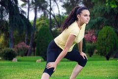 Sportvrouw het uitrekken zich benen in de zomerpark Stock Fotografie