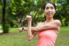 Sportvrouw het uitrekken zich wapen in park Stock Afbeeldingen