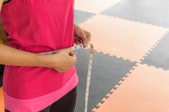 Sportvrouw met het meten van band op slank haar taille Stock Foto's