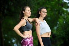 Sportvrouwen die weg in park glimlachen Stock Afbeelding
