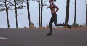 Sportvrouwjogging op plattelandsweg in ochtend stock footage