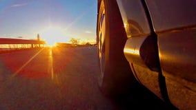 Sportwagenrennen mit Sonnenuntergang strahlt das Glänzen auf Reifen aus