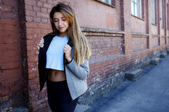 sportwear的女孩在都市红砖墙壁前面行使 Phot在一个晴朗的早晨被做了 免版税库存照片