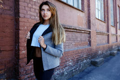 sportwear的女孩在都市红砖墙壁前面行使 Phot在一个晴朗的早晨被做了 库存照片