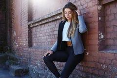 sportwear的女孩在都市红砖墙壁前面行使 Phot在一个晴朗的早晨被做了 库存图片