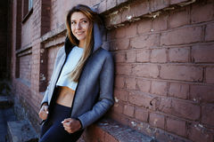 sportwear的女孩在都市红砖墙壁前面行使 Phot在一个晴朗的早晨被做了 免版税库存图片