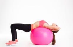 sportwear的被集中的美丽的健身女孩行使与桃红色fitball的 免版税库存照片