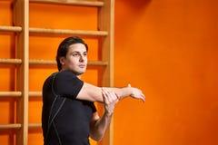 黑sportwear的运动员在做舒展的健身房行使对明亮的橙色墙壁 库存图片
