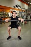黑sportwear的年轻运动人与屈曲在健身房的杠铃酒吧肌肉 免版税库存照片