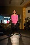 可爱的做与哑铃的桃红色sportwear的健身辅导员亚裔女孩锻炼在健身房 图库摄影