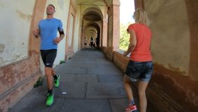 Sportwear woman running. Bologna, Italy - September 29, 2018: people running under San Luca`s portico: the longest porch in the world leading to the San Luca stock video footage