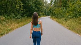 Sportwoman jogger throwing her hands while walking on forest road, enjoying freedom, believe future success. Confident