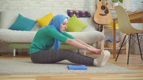 Sporty мусульманская женщина в hijab делая подогрев в современной квартире сток-видео