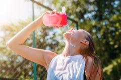 Sporty молодая белокурая женщина с sporty бутылкой с крутой освещающей водой льет воду на себе на спортивной площадке стоковые изображения