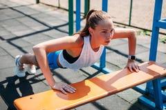 Sporty молодая сексуальная женщина делая нажим-UPS от земли спорт стенда Образ жизни принципиальной схемы здоровый стоковые фото