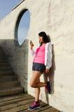 Sporty азиатская женщина принимая остатки разминки с smartphone стоковые изображения rf