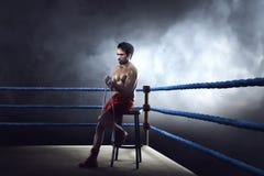 Sporty азиатский человек боксера сидя на кольце пока носящ ремень Стоковые Фото