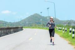 Sporty бегун женщины бежать через дорогу Разминка в парке стоковые фотографии rf
