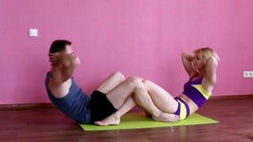 Sporty белокурая девушка и бородатый человек нагнетая подбрюшные мышцы в фитнес-клубе на розовой предпосылке