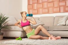 Sporty взрослая питьевая вода девушки после домашней разминки Стоковое фото RF