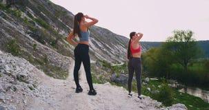 2 sporty дамы в середине изумляя ландшафта на природе остановили для перерыва смотря, что далеко увидели полностью красоту видеоматериал