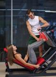 Sporty девушка делая вес работает на имитаторе с помощью ее личного тренера на спортзале скопируйте космос Стоковые Фотографии RF